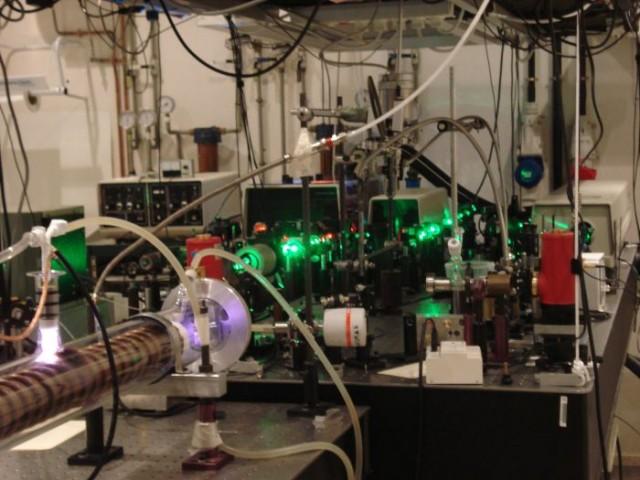 """Laboratorio de espectroscopía infrarroja de alta resolución del IEM-CSIC (Instituto de Estructura de la Materia, Consejo Superior de Investigaciones Científicas).  A la izquierda, la descarga eléctrica en cátodo hueco en la que se forma el ArH+.  Al frente, los láseres y elementos ópticos que generan la radiación infrarroja monocromática con la que se han medido las transiciones rovibracionales del ArH+"""". Créditos: IEM-CSIC"""