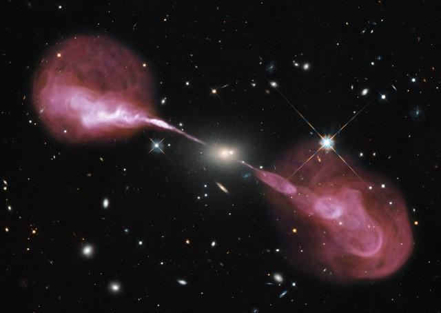 Preciosa imagen de la radiogalaxia Hércules A combinando datos ópticos obtenidos con el Telescopio Espacial Hubble con la imagen en continuo de radio proporcionada por el interferómetro Karl G. Jansky Very Large Array (JVLA, Nuevo México, EE.UU.), que aparece codificada en rosa. Hércules A está a 2 mil millones de años luz de nosotros y alberga un agujero negro súper-masivo de 2500 millones de veces la masa del Sol. Este monstruo es el responsable de los dos chorros casi simétricos de material que observamos en frecuencias de radio. Cada una de estas estructuras alcanza una distancia de unos 1.5 millones de años luz. Crédito: NASA, ESA, S. Baum and C. O'Dea (RIT), R. Perley and W. Cotton (NRAO/AUI/NSF), and the Hubble Heritage Team (STScI/AURA).