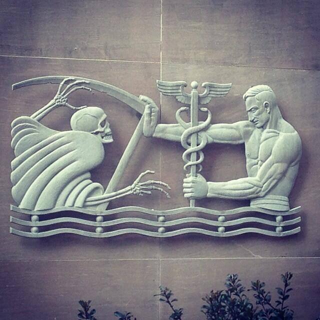 Asclepio, Esculapio para los romanos, frente a la muerte. Relieve en la fachada de la sede de los Servicios de Salud y Bienestar del Condado de Fulton