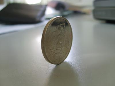 Moneda apoyada sobre su canto