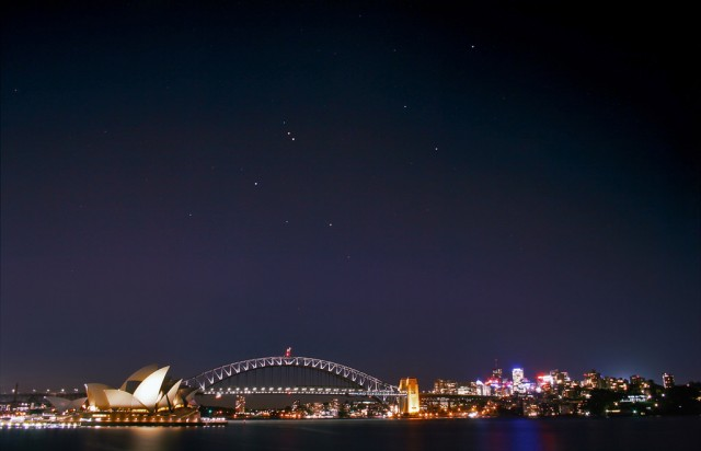 """Figura 1: La bahía de Sídney por la noche. Bonito, ¿verdad? Pues es uno de los lugares de mayor contaminación lumínica de Australia, aunque, eso sí, se queda muy corto comparando con los estándares en cualquier otra gran ciudad del mundo. Las estrellas que aparecen sobre la ciudad (la constelación de Leo con Saturno y Marte y el motivo por el que hice esta foto el 11 de julio de 2008) apenas se distinguían en las imágenes originales, que tuve que tratar con cuidado y por eso parecen tan """"artificiales"""". Más información en mi blog. Crédito: Ángel R. López-Sánchez."""