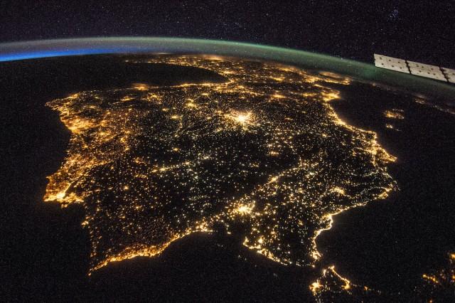 Figura 5: Fotografía de la Península Ibérica de noche obtenida por astronautas a bordo de la Estación Espacial Internacional el 26 de julio de 2014. La contaminación lumínica de nuestras ciudades y pueblos permite identificarlos fácilmente desde el espacio. Es curioso notar el cambio de iluminación entre España y Portugal. Nótese el detalle del cúmulo abierto de las Pléyades en la esquina superior derecha. Más información en este página de NASA. Crédito: NASA.