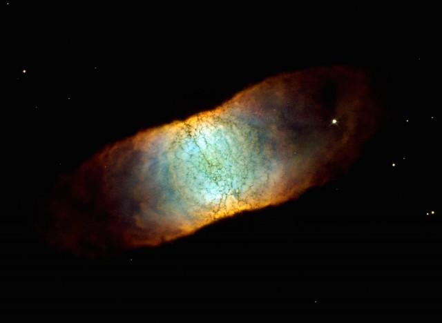 """Imagen de la Nebulosa Retina, IC 4406, una nebulosa planetaria localizada en la constelación de Lupus. Los colores codifican la emisión de [O III] (azul), H-alpha (verde) y [N II] (rojo). La alta simetría de este objeto es consecuencia de ser una estructura tipo """"donut"""" (cilindro hueco) que vemos de lado. Crédito de la imagen: C. R. O'Dell (Vanderbilt U.) et al., Hubble Heritage Team (STScI/AURA), NASA/ESA."""