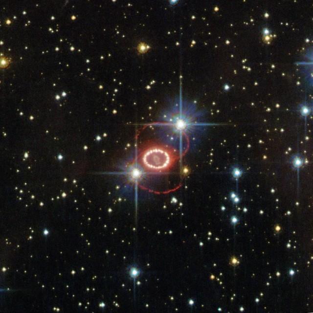 """Figura 3. Imagen del peculiar resto de supernova de SN 1987A tal y como lo observó la cámara ACS del Telescopio Espacial Hubble. Aparecen dos bucles de material difuso brillando en color rojo, con un tercer bucle en forma de anillo en su interior, todo ello rodeando a la estrella muerta en el centro. Estos tres anillos forman una estructura que ahora se conoce como """"el reloj de arena"""" de la SN 1987A. Aún no se entiende completamente bien cómo se originó esta estructura asimétrica. El campo de visión de la imagen es de sólo 25x25 segundos de arco. Crédito: ESA/Hubble & NASA."""