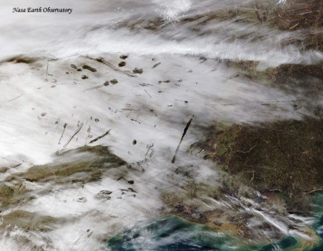Agujeros (cavum) y otras cavidades alargadas provocadas por el paso de aviones al atravesar una capa nubosa en la costa Este de los EEUU. Crédito: NASA Earth Observatory