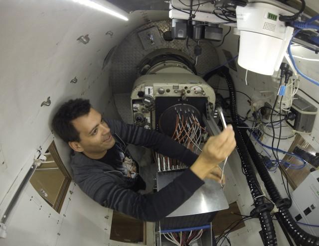"""Yo dentro de la cabina de SAMI al foco primario del Telescopio Anglo-Australiano. Tengo una de las """"hexabundles"""" en la mano mientras """"enchufo"""" con cuidado la placa a observar por el """"Muestreo de galaxias de SAMI"""" esa noche. Imagen del timelapse """"Una noche con SAMI en el Telescopio Anglo-Australiano"""". Crédito: Ángel R. López-Sánchez (AAO/MQU)."""