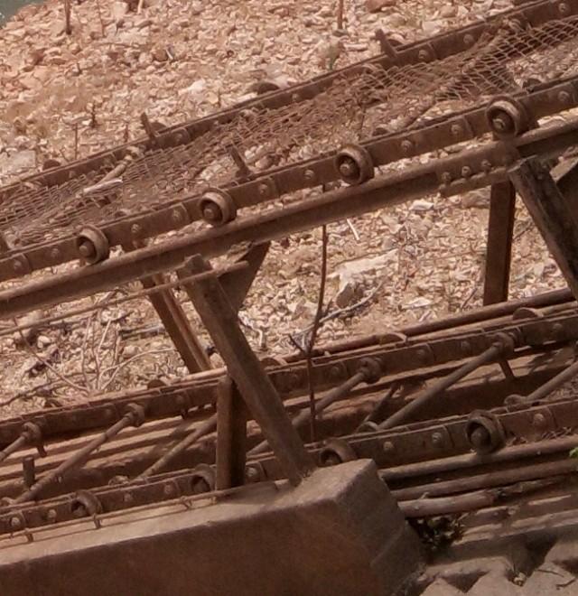 """Primer plano del mecanismo. Aún pueden apreciarse perfectamente los rodillos que permitían la circulación de las cadenas, la tela metálica que protegía el mecanismo e incluso parte de las """"garras"""" para sujetar las piezas."""