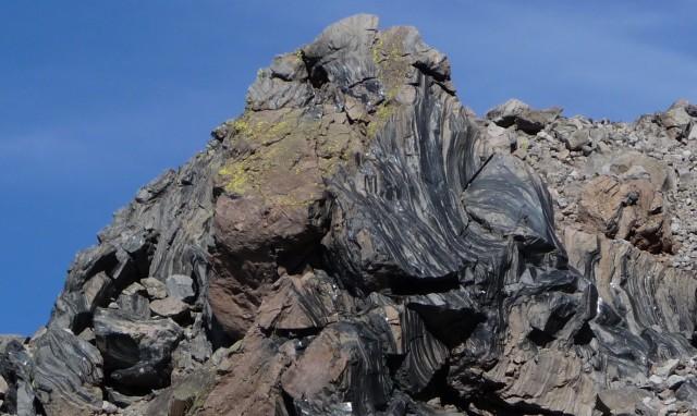 Afloramiento de obsidiana en Inyo Craters (California, EE. UU.). Se aprecian claramente unos niveles alternantes de color negro y de color gris, debido a un bandeado de flujo que se origina por variación en la concentración de microcristales. Las manchas pardas están producidas por meteorización superficial. Autor: Daniel Mayer