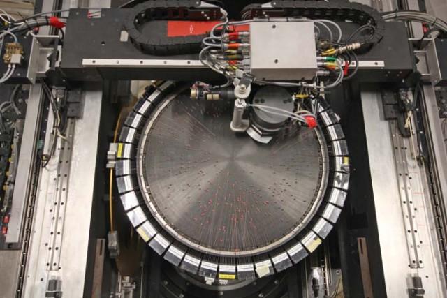 """Figura 2. El robot 2dF del Telescopio Anglo-Australiano moviendo fibras ópticas, que están iluminadas en rojo. Esta imagen es un fotograma del vídeo timelapse """"Una noche con 2dF en el AAT"""". Crédito: Ángel R. López-Sánchez (AAO/MQU)."""